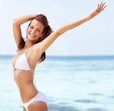 Smilende brunette i hvid bikini på strand