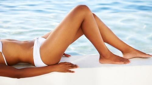 Kvinde i hvid bikini liggende i vandkant