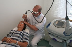 Erik Obitz udfører laserbehandling for kunde