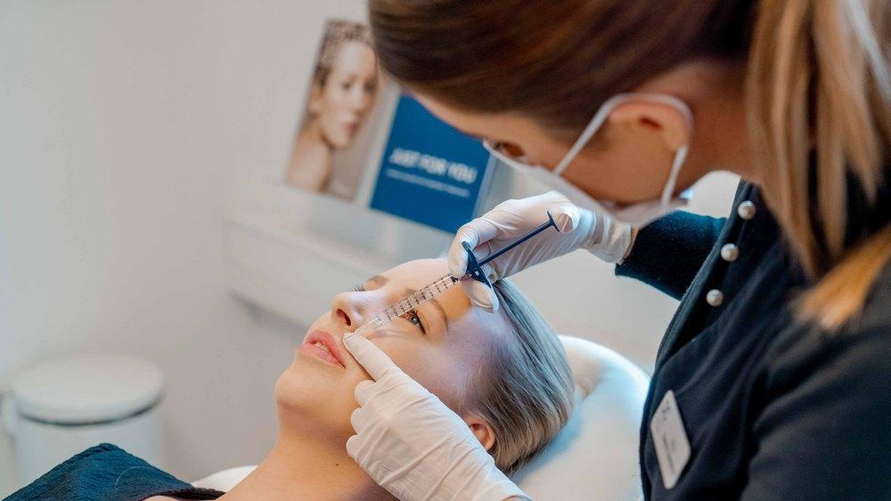 Behandler udfører ansigtsbehandling med injektionssprøjte