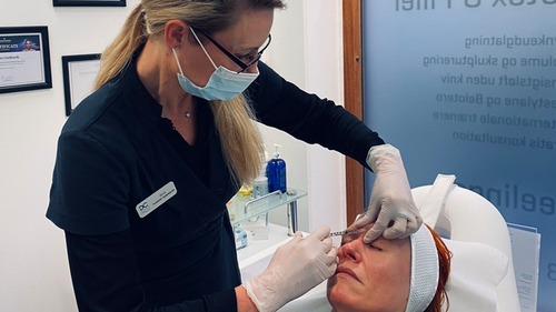 Behandler udfører ansigtbehandling